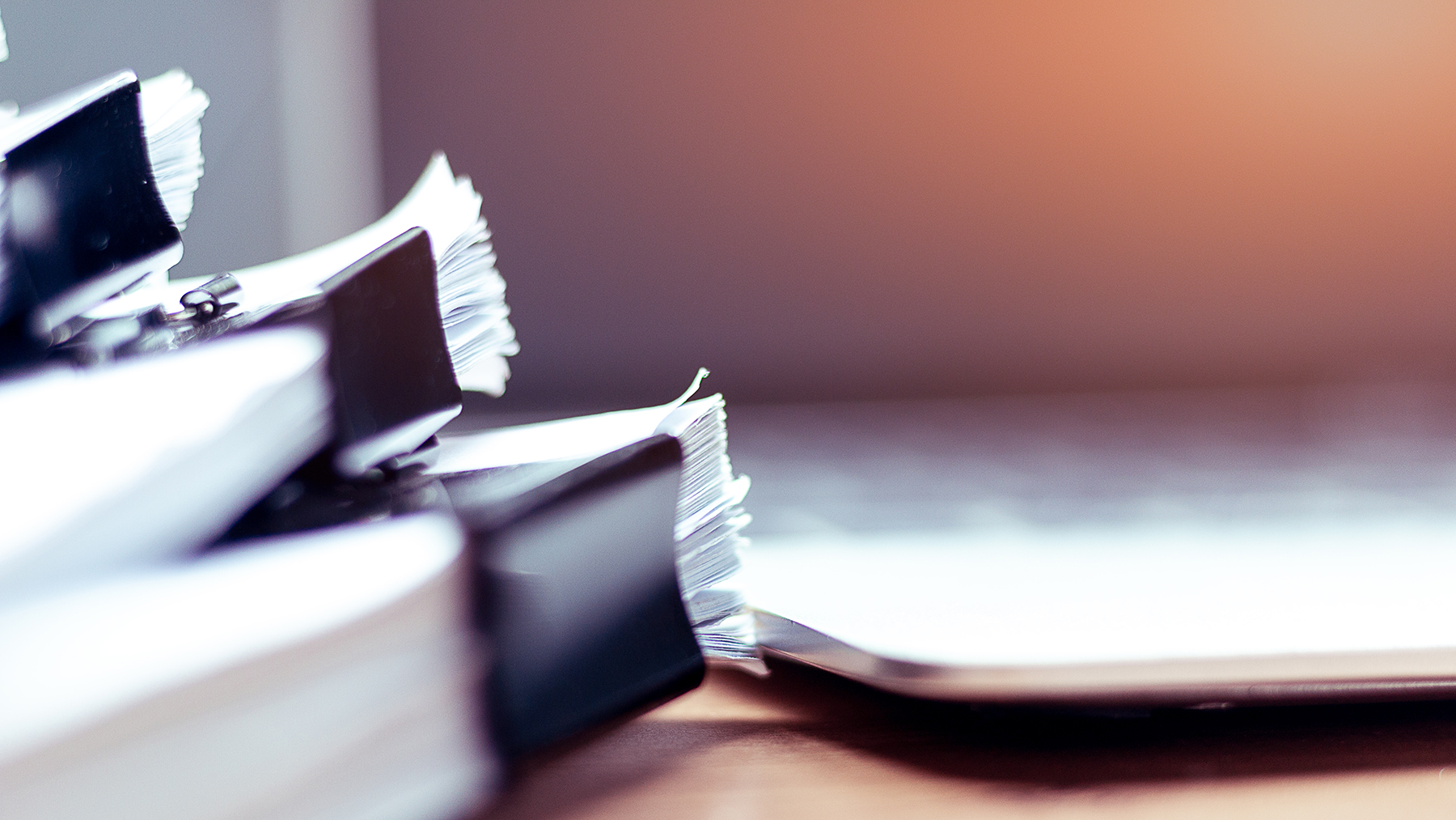 Stack of papers in front of computer