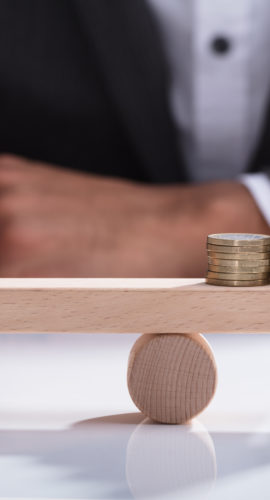 Close-up Of A Businessperson's Hand Balancing Stacked Coins On Wooden Seesaw With Finger Over Desk